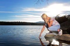 Nastoletnia dziewczyna na skale jeziorem zdjęcie royalty free