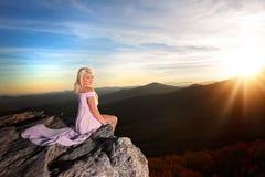 Nastoletnia dziewczyna na skale przegapia w górach obraz royalty free