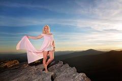 Nastoletnia dziewczyna na skale przegapia w górach fotografia stock