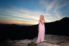 Nastoletnia dziewczyna na skale przegapia w górach zdjęcie royalty free