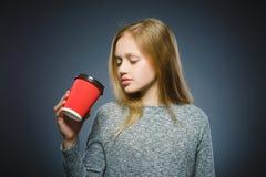 Nastoletnia dziewczyna napoju czerwona filiżanka kawy odizolowywająca na szarym tle fotografia stock