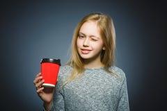 Nastoletnia dziewczyna napoju czerwona filiżanka kawy odizolowywająca na szarym tle zdjęcie royalty free