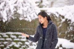 Nastoletnia dziewczyna outdoors zbroi szeroko rozpościerać cieszący się opad śniegu w zimie zdjęcie stock