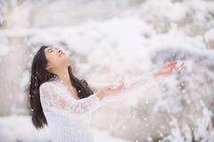 Nastoletnia dziewczyna outdoors zbroi szeroko rozpościerać cieszący się opad śniegu w zimie obrazy stock