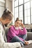 Nastoletnia dziewczyna patrzeje jej troskliwego ojca z ładną fryzurą fotografia stock