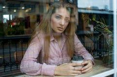 Nastoletnia dziewczyna patrzeje kamerę w okno fotografia stock
