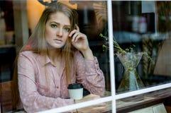 Nastoletnia dziewczyna patrzeje kamer? w okno zdjęcia stock