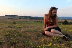 Nastoletnia dziewczyna patrzeje kwiaty w jej butach zdjęcie royalty free