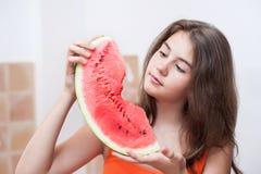 Nastoletnia dziewczyna patrzeje plasterek arbuz w pomarańczowej koszulce Zdjęcia Royalty Free