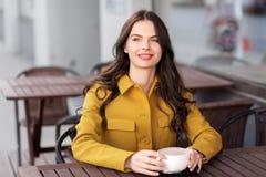 Nastoletnia dziewczyna pije gorącą czekoladę przy miasto kawiarnią zdjęcia royalty free