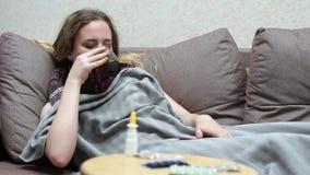 Nastoletnia dziewczyna pije medycyny herbaty ciepłej Kłamający na leżance, zakrywającej z koc zdjęcie wideo