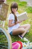 Nastoletnia dziewczyna pozuje z bicyklem na tle ogród Zdjęcie Stock