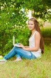 Nastoletnia dziewczyna pracuje z laptopem na trawie Obraz Stock