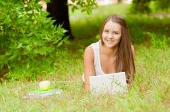 Nastoletnia dziewczyna pracuje z laptopem na trawie Zdjęcie Stock