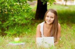 Nastoletnia dziewczyna pracuje z laptopem na trawie Fotografia Stock