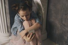 Nastoletnia dziewczyna przesadnie siedzi przy telefonem w domu jest ofiarą online ogólnospołeczne sieci Smutny nastoletni sprawdz fotografia stock