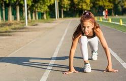 Nastoletnia dziewczyna przy początkiem dla biegać w stadium obraz stock