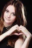 Nastoletnia dziewczyna robi kierowemu kształt miłości symbolowi z rękami Obrazy Stock