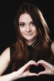 Nastoletnia dziewczyna robi kierowemu kształt miłości symbolowi z rękami Fotografia Stock