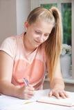 Nastoletnia dziewczyna robi pracie domowej przy stołem obrazy stock