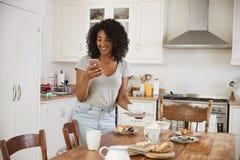 Nastoletnia Dziewczyna Rozjaśnia Śniadaniowego stół I Sprawdza telefon komórkowego zdjęcie royalty free