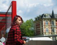 Nastoletnia dziewczyna słucha muzyka w szkockiej kraty koszula podczas gdy czekający autobus obraz royalty free