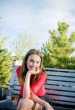 Nastoletnia dziewczyna siedzi uśmiechniętego outside Obraz Royalty Free