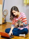 Nastoletnia dziewczyna używa notatnika w jej pokoju podczas gdy trzymający psiego szczeniaka Zdjęcia Royalty Free