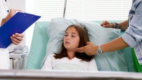 Nastoletnia dziewczyna w łóżka szpitalnego odpowiadania lekarki pytaniach zbiory