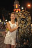 Nastoletnia dziewczyna w biel sukni obok rzeźby lew Zdjęcia Royalty Free
