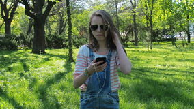 Nastoletnia dziewczyna w hełmofonach Dziewczyna słucha muzyka w okularach przeciwsłonecznych z telefonem i dzień pogodny parkowy zbiory wideo
