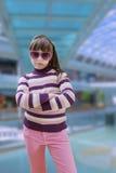 Nastoletnia dziewczyna w menchiach jest ubranym okulary przeciwsłonecznych z nowożytnym Zdjęcia Stock