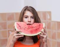 Nastoletnia dziewczyna w pomarańczowej koszulce cieszy się jedzący plasterek arbuz Obraz Royalty Free