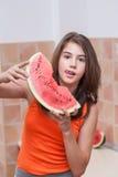 Nastoletnia dziewczyna w pomarańczowej koszulce pokazuje plasterek arbuz Obraz Stock