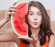 Nastoletnia dziewczyna w pomarańczowej koszulce pokazuje plasterek arbuz Zdjęcia Stock