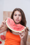 Nastoletnia dziewczyna w pomarańczowej koszulce pokazuje plasterek arbuz Obrazy Royalty Free