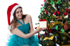 Nastoletnia dziewczyna w Santa kapeluszowej ofiary teraźniejszej poniższej choince Fotografia Royalty Free
