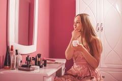 Nastoletnia dziewczyna w smokingowym kładzeniu śmietanka na twarzy, narządzanie dla makeup obraz stock