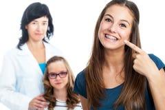 Nastoletnia dziewczyna wskazuje przy stomatologicznymi barces z lekarką w tle Zdjęcia Royalty Free