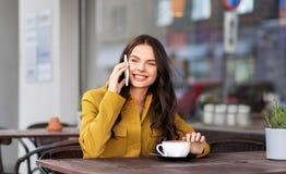 Nastoletnia dziewczyna wzywa smartphone przy miasto kawiarnią zdjęcia stock