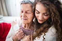Nastoletnia dziewczyna z babcią w domu, ściskający obrazy royalty free