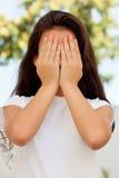 Nastoletnia dziewczyna z dwanaście lat zakrywa jej twarz zdjęcie stock