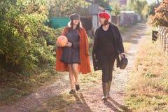 Nastoletnia dziewczyna z jej mamą iść na wiejskim śladzie z banią i słonecznikiem w rękach obrazy royalty free