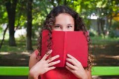 Nastoletnia dziewczyna z kędzierzawego włosy czytelniczą książką Obrazy Royalty Free