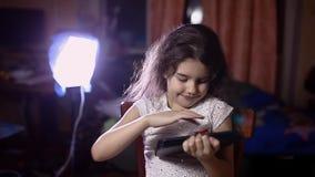Nastoletnia dziewczyna z pastylką w izbowym wyszukuje internecie zbiory wideo