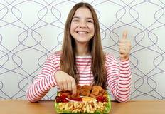 Nastoletnia dziewczyna z smakowitymi kurczak bry?kami, kciukiem w g?r? i zdjęcia stock