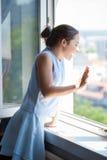 Nastoletnia dziewczyny fala na okno Obrazy Stock