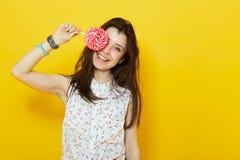 Nastoletnia kobieta uśmiecha się lizaka i trzyma Zdjęcie Royalty Free