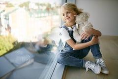 Nastoletnia piękna dziewczyna w cajgach odziewa blisko okno z niedźwiedziem Obraz Royalty Free