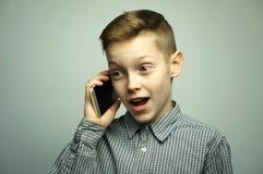 Nastoletnia poważna chłopiec opowiada na smartphone z eleganckim ostrzyżeniem Fotografia Royalty Free